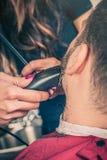 Fryzjer męski broda ciie klienta brodę z drobiażdżarką Obrazy Stock