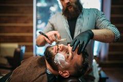 Fryzjer męski goli brodę klient przy zakładem fryzjerskim Fotografia Stock