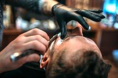 Fryzjer męski goli brodę prostą żyletką Obraz Stock