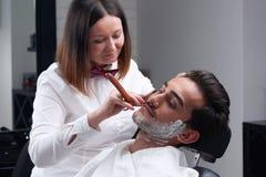 Fryzjer męski kobiety ogoleń broda z żyletką i golenie pienimy się Obrazy Stock