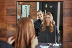 Fryzjer męski opowiada młoda piękna dziewczyna w piękno salonie Zdjęcie Stock