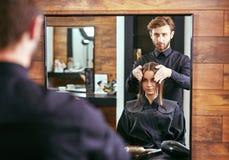 Fryzjer męski opowiada młoda piękna dziewczyna w piękno salonie Fotografia Stock