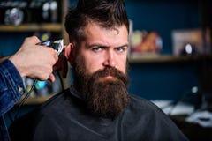 Fryzjer męski pracy z włosianym cążki Zakładu fryzjerskiego pojęcie Ręki fryzjer męski z cążki, zamykają up Modnisia brodaty klie Obrazy Stock