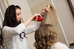 Fryzjer męski robi dziewczyny fryzurze przy piękno salonem Zdjęcia Stock