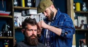 Fryzjer męski w drelichowej kurtce ruchliwie z arymażu modnisiem, zakładu fryzjerskiego tło Klient z brodą i wąsy zakrywający z Fotografia Stock