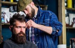 Fryzjer męski w drelichowej kurtce ruchliwie z arymażu modnisiem, zakładu fryzjerskiego tło Klient z brodą i wąsy zakrywający z Obrazy Stock