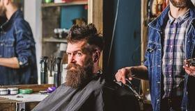 Fryzjer męski z cążki i brutalnym brodatym klientem Modnisia klient dostaje ostrzyżenie Modnisia stylu życia pojęcie Fryzjer męsk fotografia royalty free