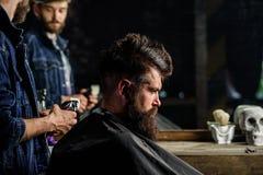 Fryzjer męski z cążki tytułowania włosy brutalny brodaty klient Modnisia stylu życia pojęcie Fryzjer męski z włosianego cążki pra Fotografia Royalty Free