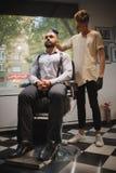 Fryzjer męski z hairbrush pracuje na nowym ostrzyżeniu dla klienta Brodaty klient przy zakładu fryzjerskiego tłem kosmos kopii Fotografia Royalty Free
