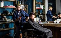 Fryzjer męski z hairdryer pracuje na fryzurze dla brodatego mężczyzna zakładu fryzjerskiego tła Fryzjer męski z hairdryer suszarn Zdjęcia Stock