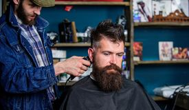 Fryzjer męski z włosianym cążki pracuje na fryzurze dla brodatego faceta zakładu fryzjerskiego tła Modnisia stylu życia pojęcie b Fotografia Royalty Free