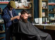 Fryzjer męski z włosianym cążki pracuje na ostrzyżeniu brodaty facet, retro zakładu fryzjerskiego tło Modniś fryzury pojęcie Zdjęcia Stock
