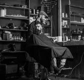 Fryzjer męski z włosianym cążki w ręce kończył żyłować Modnisia klient dostaje ostrzyżenie Fryzjer męski z włosianego cążki praca obraz royalty free