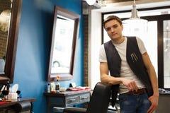 Fryzjer męski zaprasza mieć siedzenia na krześle przy zakładem fryzjerskim Obrazy Royalty Free