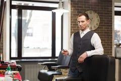 Fryzjer męski zaprasza mieć siedzenia na krześle przy zakładem fryzjerskim Zdjęcie Royalty Free