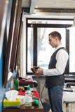 Fryzjer męski zaprasza mieć siedzenia na krześle przy zakładem fryzjerskim Fotografia Stock