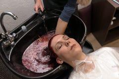 Fryzjer myje klient kobiety głowę na specjalnym zlew po farbować włosy w fryzjera salonie zdjęcie stock