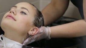 Fryzjer myje młodej kobiety ` s włosy w salonie w rękawiczkach zbiory