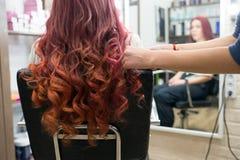 Fryzjer ręki robią formacji kędziory długie włosy na głowie klient w salonie fotografia royalty free