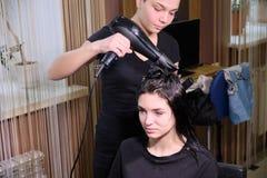 Fryzjer robi fryzury brunetki dziewczyny w pi?kno salonie z hairdryer obrazy stock