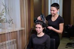 Fryzjer robi fryzury brunetki dziewczyny w pi?kno salonie z hairdryer zdjęcie stock