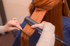 Fryzjer robi fryzury dziewczyny z długim czerwonym włosy w piękno salonie Obraz Royalty Free