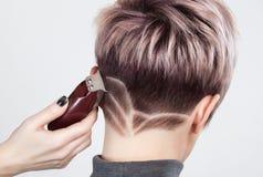 Fryzjer robi kreatywnie ostrzyżeniu z żyletką piękna kobieta obraz stock