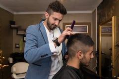 Fryzjer Robi ostrzyżeniu młody człowiek Zdjęcia Royalty Free