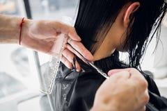 Fryzjer robi ostrzyżeniu z nożycami włosy młoda dziewczyna w piękno salonie obraz royalty free