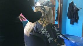 Fryzjer robi podkreślać dziewczyna używa narzędzia i folię zdjęcie wideo
