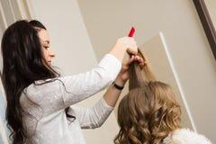 Fryzjer robi włosianej tytułowanie dziewczyny w studiu Obraz Royalty Free