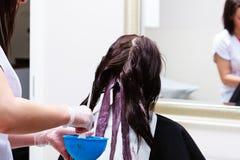 Fryzjer stosuje koloru żeńskiego klienta przy salonem, robi włosianemu barwidłu obrazy royalty free