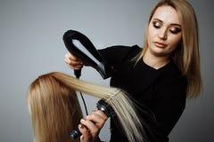 Fryzjer suszy włosy z hairdryer w piękno salonie obraz royalty free