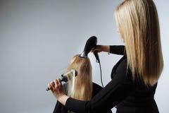 Fryzjer suszy włosy z hairdryer w piękno salonie obrazy royalty free