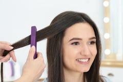 Fryzjer używa nowożytnego mieszkania żelazo projektować klienta włosy obraz royalty free