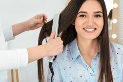 Fryzjer używa nowożytnego mieszkania żelazo projektować klienta włosy zdjęcie royalty free