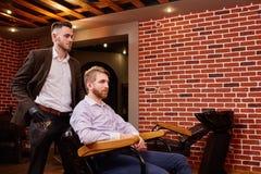 Fryzjer z fryzjerem męskim wytłacza wzory pozycję blisko mężczyzna obsiadania na krześle przeciw ściana z cegieł Obraz Royalty Free