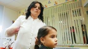 Fryzjer z małą dziewczynką Śmieszny dzieciak w fryzjerstwo salonie zbiory wideo