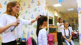 Fryzjer z małą dziewczynką Śmieszny dzieciak w fryzjerstwo salonie Naprawiania ponytail z lakier do włosów zbiory