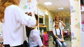 Fryzjer z małą dziewczynką Śmieszny dzieciak w fryzjerstwo salonie Robić ponytale zdjęcie wideo