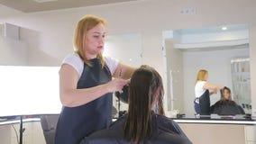 Fryzjera czesanie i cuting włosy nastoletni dziewczyna klient w włosianym salonie zdjęcie wideo