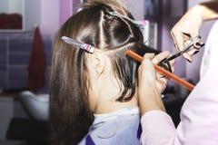 Fryzjera rżnięty brown włosy w rękach grępla i nożyce obrazy stock