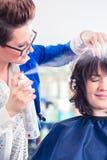 Fryzjera tytułowania kobiety włosy w sklepie obrazy royalty free
