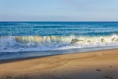 Fryzowania ?amania fali tubka, pieni si? z backwash na piaskowatym brzeg obrazy royalty free