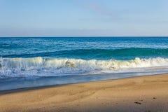 Fryzowania łamania fali tubka, pieni się z backwash, z nadchodzącym pęcznieniem na piaskowatym brzeg, zdjęcie royalty free