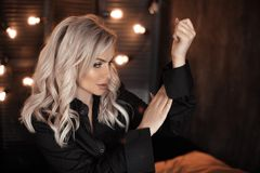 fryzury Piękny blondynki kobiety portret pozuje w czarnej koszula Modny blond dziewczyna model nad bokeh zaświeca ciemnego tło zdjęcia royalty free