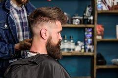Fryzury usługowy pojęcie Modnisia brodaty klient dostać fryzurę Fryzjer męski z cążki pracuje na fryzurze dla brodatego mężczyzna Zdjęcia Royalty Free