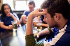 Fãs de futebol que olham o fósforo de futebol na barra ou no bar Fotografia de Stock