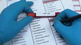 FSH, Doktor, der Hormonnamen im Laborfreien raum, Blutprobe im Rohr zeigend überprüft stock footage