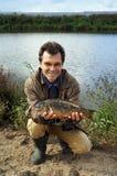 Fsherman con la carpa a specchi del pesce Immagine Stock
